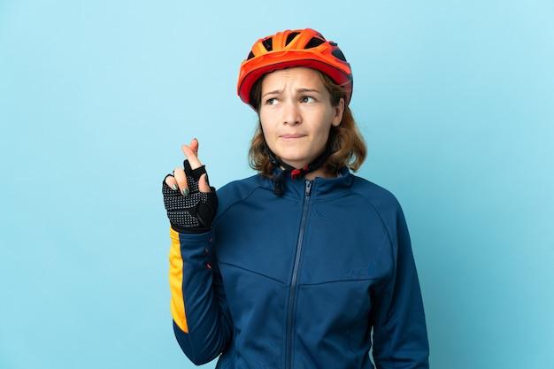 Молодая женщина-велосипедист изолирована на синем фоне со скрещенными пальцами и желает лучшего