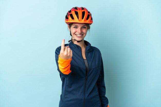 Молодая женщина-велосипедист, изолированная на синем, делает приближающийся жест