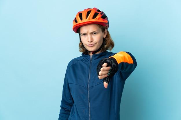 부정적인 표현으로 아래로 엄지 손가락을 보여주는 파란색에 고립 된 젊은 사이클 여자