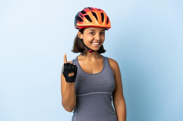 Молодая женщина-велосипедист изолирована на синей стене, делая приближающийся жест