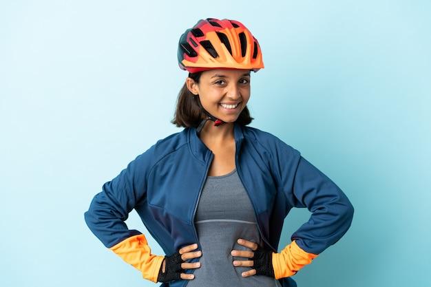 엉덩이에 팔을 포즈와 미소 파란색 벽에 고립 된 젊은 사이클 여자