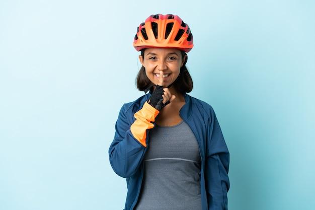 입에 손가락을 넣어 침묵 제스처의 표시를 보여주는 파란색 벽에 고립 된 젊은 사이클 여자