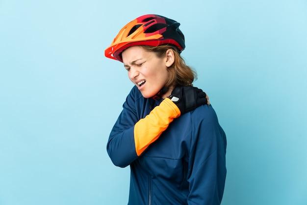 努力したために肩の痛みに苦しんで青い壁に孤立した若いサイクリストの女性