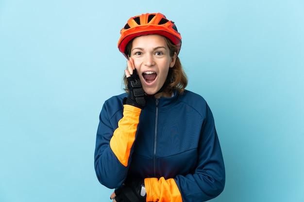 Молодая велосипедистка изолирована на синей стене с удивленным и шокированным выражением лица