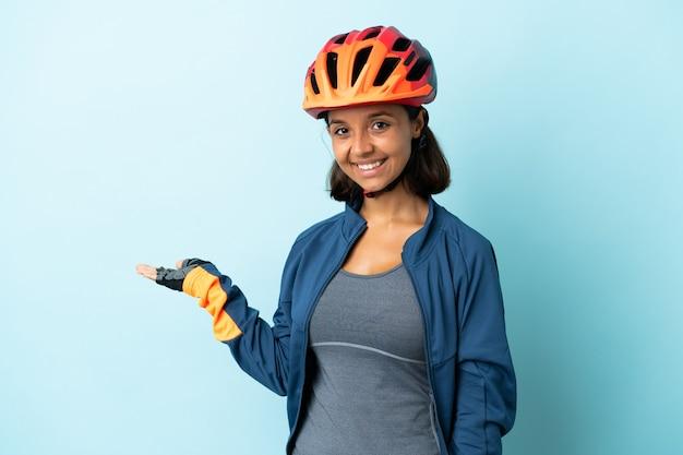 Молодой велосипедист женщина на синем, протягивая руки в сторону для приглашения приехать