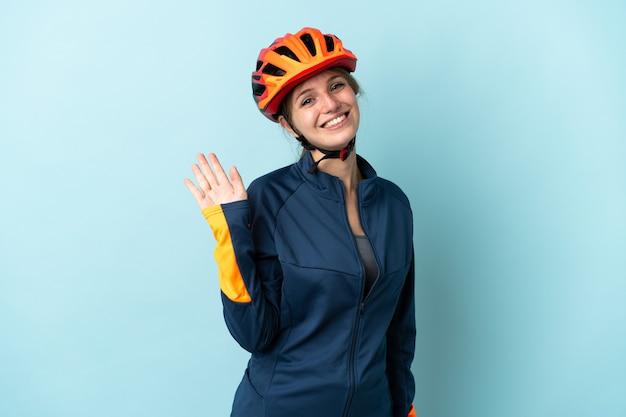 幸せな表情で手で敬礼する青い上の若いサイクリストの女性