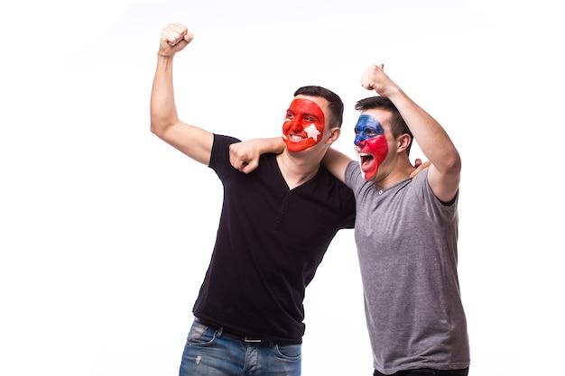 若いチェコとチュニジアのサッカーファンは、白い壁に孤立した感情を勝ち負けます