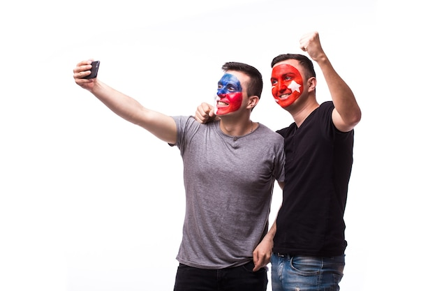 Young czech and tunisian football fans take selfie isolated on white wall