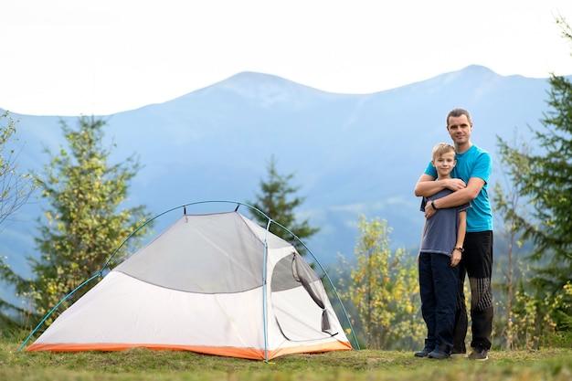 젊은 아빠와 그의 자식 아들이 함께 여름 산에서 하이킹을 하고 있습니다. 활동적인 가족 여행 컨셉입니다.