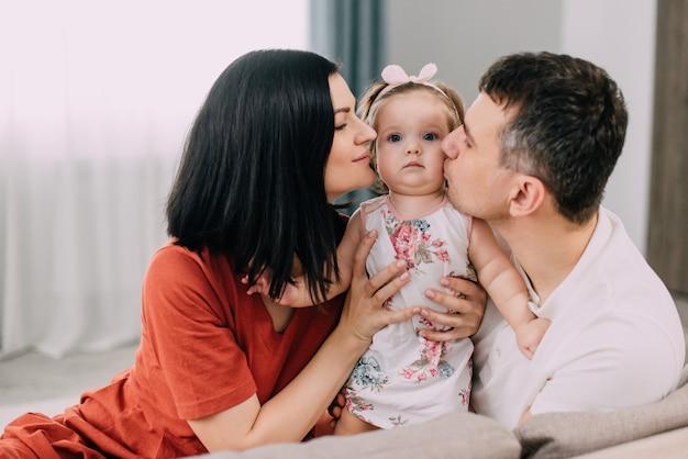 Молодые папа и мама обнимают годовалую дочь, сидя на диване у себя дома.