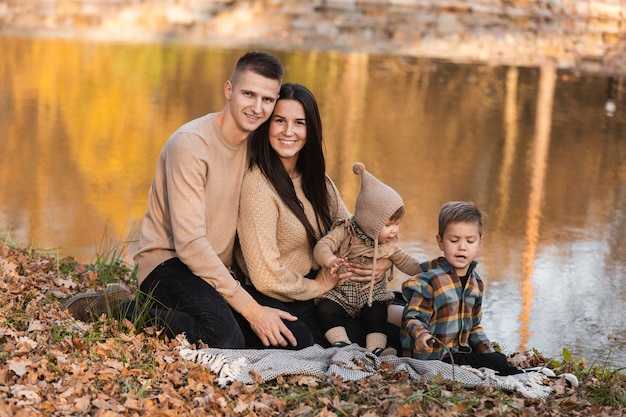 Молодой папа и мама с девочкой и маленьким сыном веселятся на одеяле возле пруда в осеннем парке