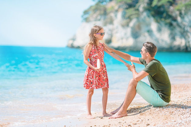 ビーチで娘の鼻に日焼け止めを適用する若いお父さん。日焼け止め