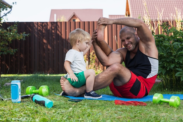 家の近くの庭で暖かい日にマットの上で彼の小さな陽気な息子と一緒に若いお父さんの運動選手はスポーツに行き、ヨガをし、彼の頭の上に彼の足を投げます