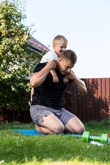 家の近くの庭で暖かい日にマットの上で彼の小さな陽気な息子と一緒に若いお父さんの運動選手はスポーツに行きます