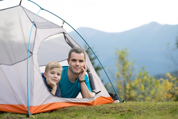 Young dad and his child son hiking together in summer mountains. active family travelling concept.