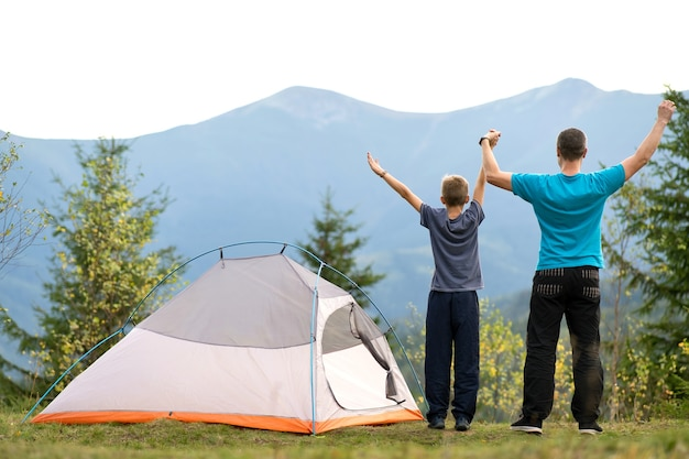 Young dad and his child son standing near camping tent with raised hands while hiking together in summer mountains.