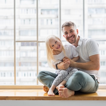 Young dad holding her 3,5 years old daughter while sitting on window sill.