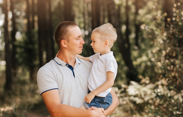 A young dad holds his young son in his arms and looks at the unlunted in nature.