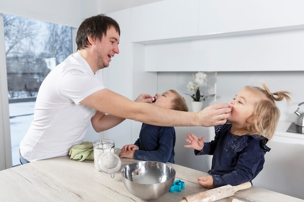 A young dad is feeding small children in the kitchen. fun time together.