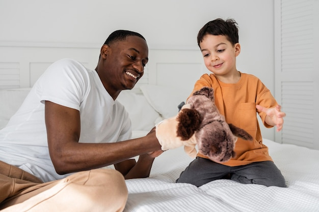 Young dad paying with toys his kid