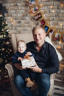 Young dad sits with his little son with a present