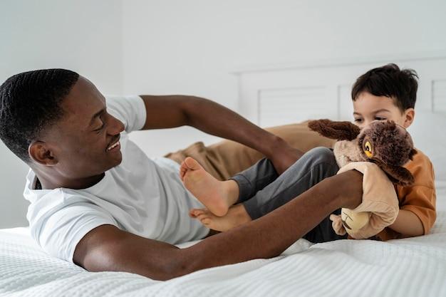 若いお父さんは遊んでいる間彼の子供をくすぐった