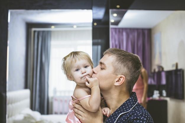 寝室で娘の小さな子供と一緒に抱きしめ、幸せな若いお父さん
