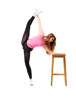 Young dance girl over isolated white background stretching