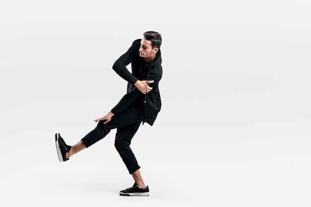 スタイリッシュな黒い服を着た若いダンサーがストリートダンスを踊りながら片足を持ち上げる