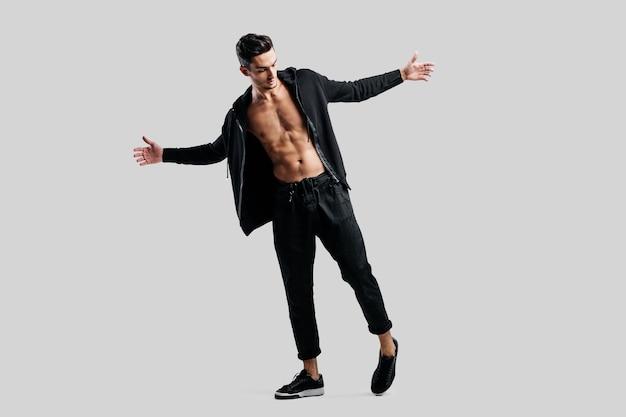 黒のズボンと裸の胴体にスウェットシャツを着た若いダンサーが立って、腕を横に広げます