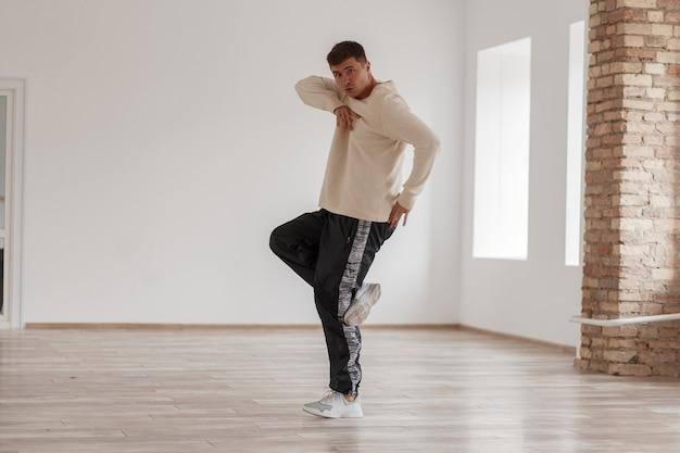 얼굴 근처에 손을 잡고 흰색 운동화에 젊은 댄서 남자가 제대로 춤을 추는 방법을 보여줍니다.