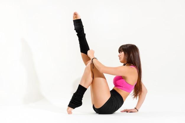 Молодая танцовщица натягивает танцевальные носки до щиколотки крупным планом, вид сбоку, сидя на земле, изолированной на белом с тенью и copyspace