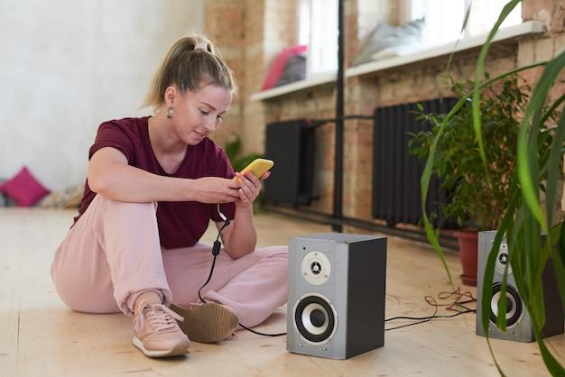 スタジオで彼女のダンスのための音楽を探している彼女の携帯電話を使用して床に座っている若いダンサー