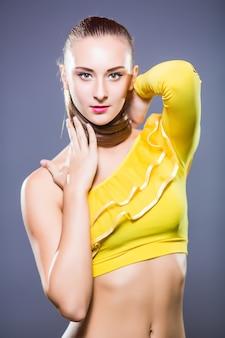 Молодой танцор со спортивным телом позирует в студии на белом фоне