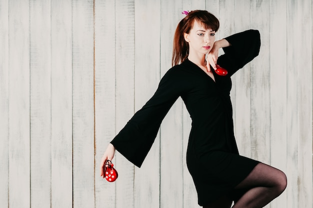 A young dancing girl in black dress, with castanets, light background
