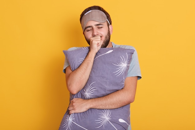 Young dark haired and bearded male yawning and covering mouth with his fist, keeps eyes closed, hugs a pillow