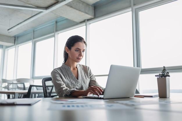 縞模様のシャツを着た若い黒髪の実業家は、彼女のオフィスに座って、ラップトップを調べています。彼女のノートと鉛筆は机の上に横たわっています。明るくモダンなオフィス。