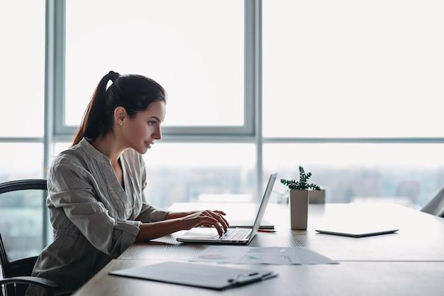縞模様のシャツを着た若い黒髪の実業家は、彼女のオフィスに座って、ラップトップを調べています。必要な書類が机の上にあります。明るくモダンなオフィス。