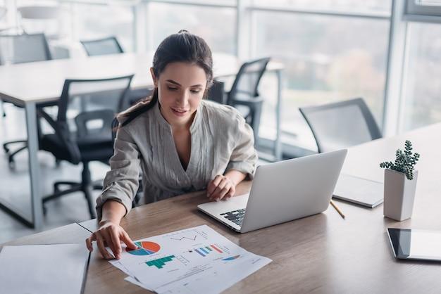 Молодая темноволосая бизнес-леди в полосатой рубашке сидит в своем офисе и просматривает графики. ее ноутбук, телефон, блокнот и карандаш лежат на столе. просторный светлый современный офис.