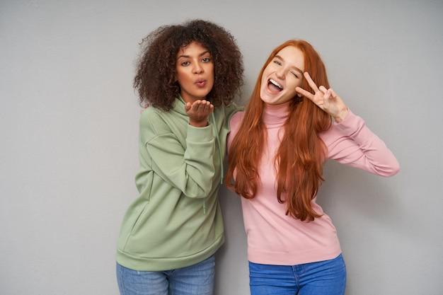 勝利のジェスチャーを示す陽気な若いかなり赤毛の女性と灰色の壁の上にポーズをとっている間、空気のキスを吹く暗い肌を持つ若い黒髪の巻き毛の女性