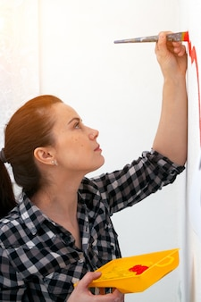 Young dark-haired female mom in plaid shirt draws on a white wall