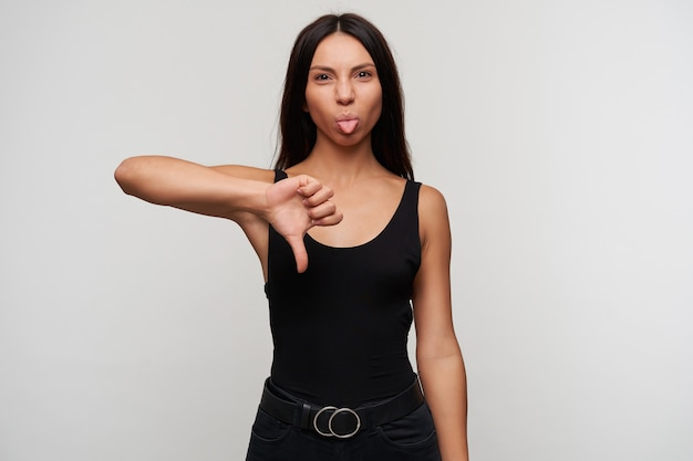 Young dark haired female with casual hairstyle raising hand in dislike gesture while posing, puckering and showing tongue