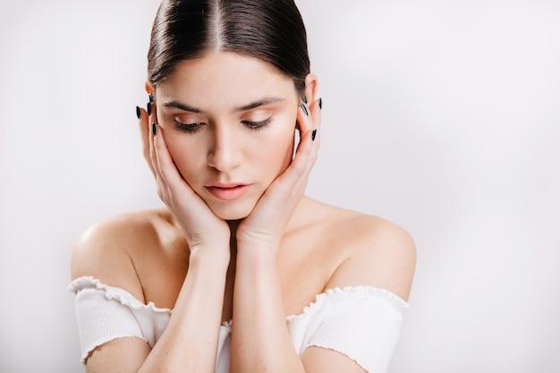 Giovane ragazza dai capelli scuri con pelle pulita senza trucco guarda verso il basso, toccando il suo viso sulla parete isolata.