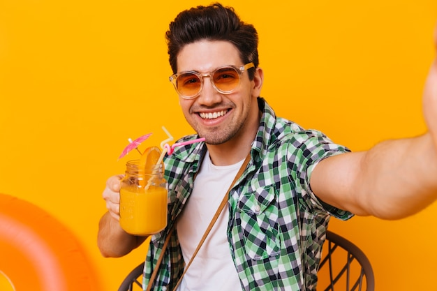 Young dark-haired guy in green shirt and orange glasses enjoys cocktail and takes selfie on isolated space.