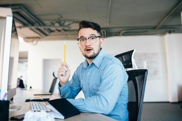 안경에 검은 머리 젊은이 사무실에서 직장에 앉아있다. 그는 파란색 셔츠를 입는다. 그는 연필을 들고 카메라를 바라보고있다.