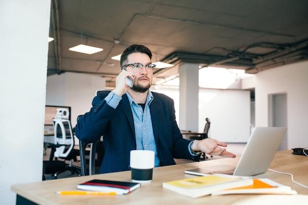 若い黒髪の男はオフィスのテーブルで働いています。彼は黒いジャケットの青いシャツを着ています。彼は電話で話していて、道に迷っています。