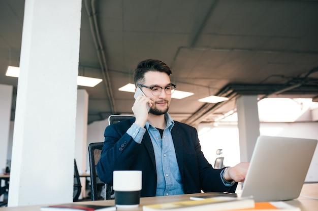 검은 머리 젊은이 사무실에있는 테이블에서 일하고있다. 그는 검은 색 재킷에 파란색 셔츠를 입는다. 그는 전화로 말하고 노트북에 보여줍니다.