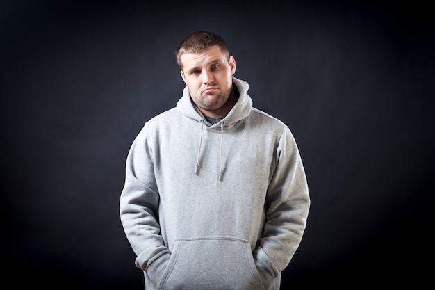 A young dark-haired man in a sports gray sweatshirt was upset that he fell ill and looks sad