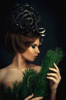 가문비 나무로 만든 창조적 인 드레스를 입고 포즈를 취하는 젊은 검은 머리 모델