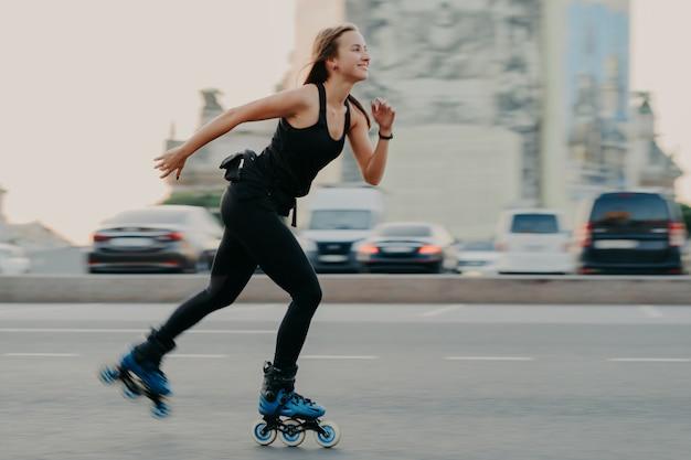 Молодая темноволосая стройная здоровая женщина имеет время восстановления, любит кататься на роликах на скорости, быстро движется, имеет веселое выражение лица, носит черную футболку и леггинсы. концепция активного отдыха и спортивной тренировки